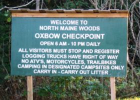"Sign: ""Welcome to North Maine Woods, Oxbow Checkpoint . . . ."""